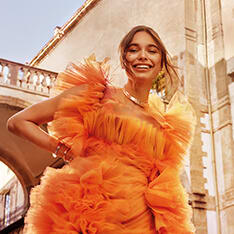 Smiling model holding the Bvlgari Rock'n'Rome Bvlgari Allegra fragrance flacon in orange and purple glass, and wearing B.zero1 jewels.