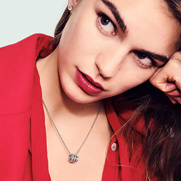 Model wearing a Serpenti Viper pendant necklace in white gold with diamonds, close up.