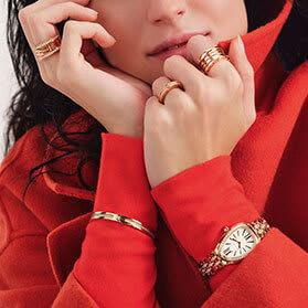 Model wearing B.zero1 and Serpenti Viper rose gold rings, a Serpenti Seduttori rose gold and diamond watch, and a B.zero1 bangle, close up.
