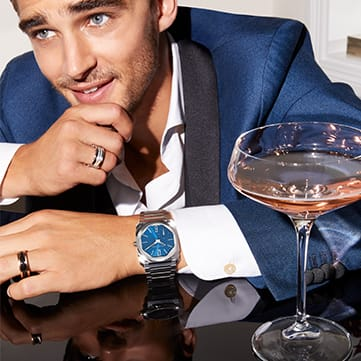 Polaroid depicting a model with a cocktail wearing an Octo Finissimo Automatic steel watch with blue dial and B.zero1 rings.