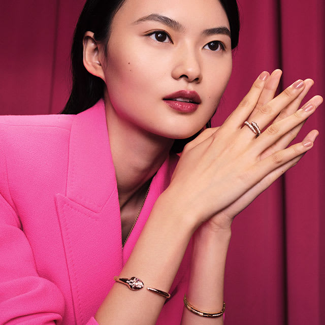 Model wearing a rose gold Serpenti Viper ring and bangle with diamonds and a B.zero1 yellow gold bangle.