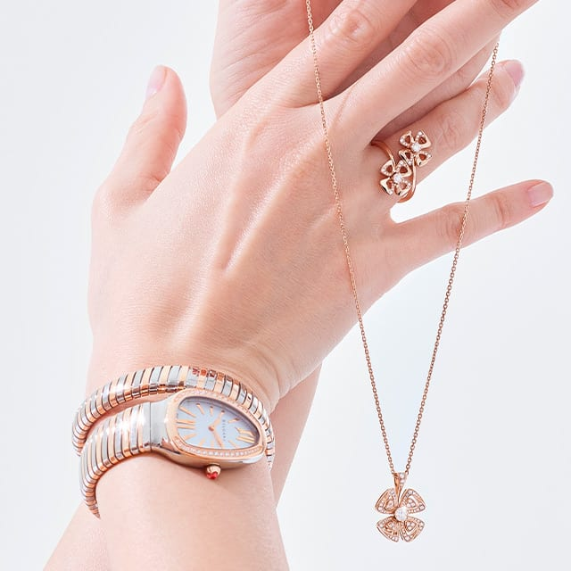 Model wearing Fiorever rings and necklace in rose gold with diamonds and Serpenti tubogas watch.