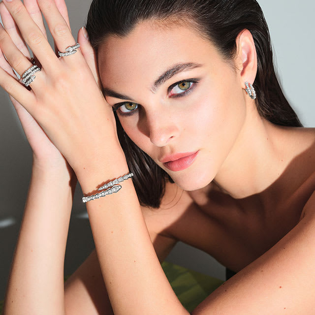 Model wearing Serpenti Viper white gold earrings, rings and a bracelet with diamonds and a Serpenti Viper rose gold bracelet, close up.