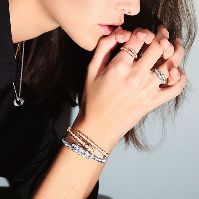Vittoria Ceretti wearing Serpenti Viper white gold earrings, rings and a bracelet with diamonds and a Serpenti Viper rose gold bracelet, close up.