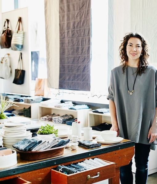 A woman standing in a fashion boutique looking to camera