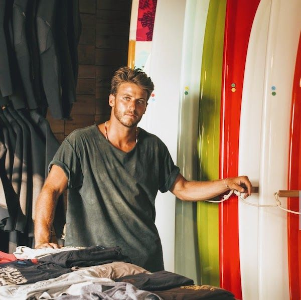 A young man in a surfboard shop looking to camera