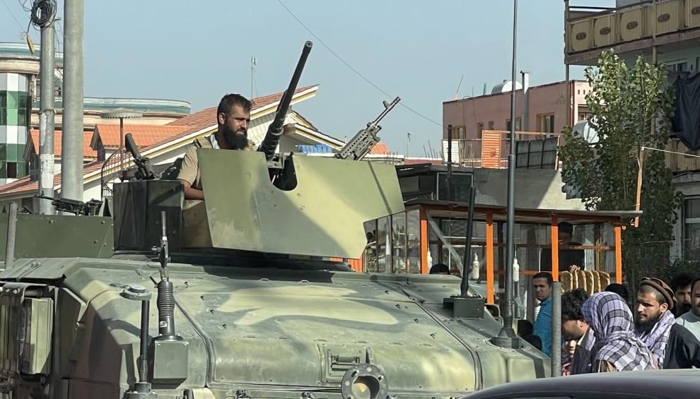 Homem em um tanque de guerra nas ruas da capital do Afeganistão.