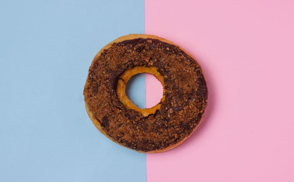 donut marrom com um fundo azul e rosa
