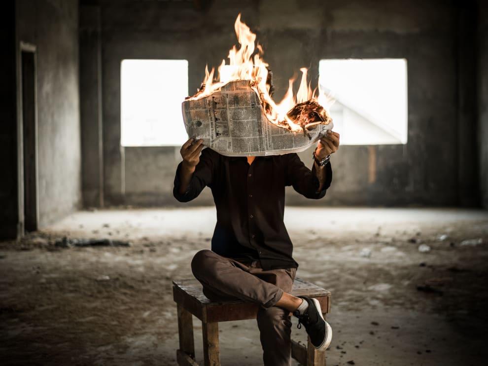 Uma pessoa lendo um jornal pegando fogo