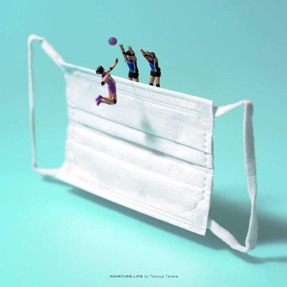 Uma máscara servindo de papel de rede, para três miniaturas: duas fazem o bloqueio do volei, enquanto outra corta.