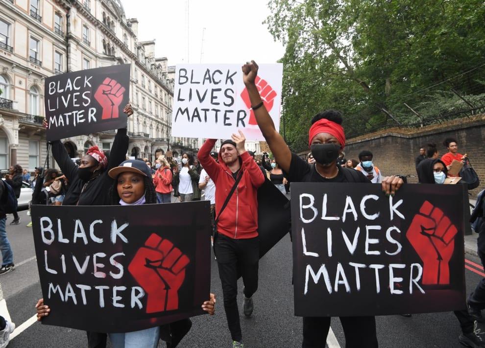 """Jovens protestam na rua com cartazes escritos """"Black Lives Matter"""". Uma mulher usando boné segura um cartaz. Ao seu lado outra mulher usando turbante vermelho, máscara preta segura um cartaz igual. Atrás delas, um homem branco de blusa vermelha leva um cartaz idêntico, porém o cartaz dele é feito de papel branco (o delas é de papel preto). Ao lado desse homem, outra mulher negra leva o cartaz com os mesmos dizeres. Atrás deles, várias outras pessoas protestam juntas."""
