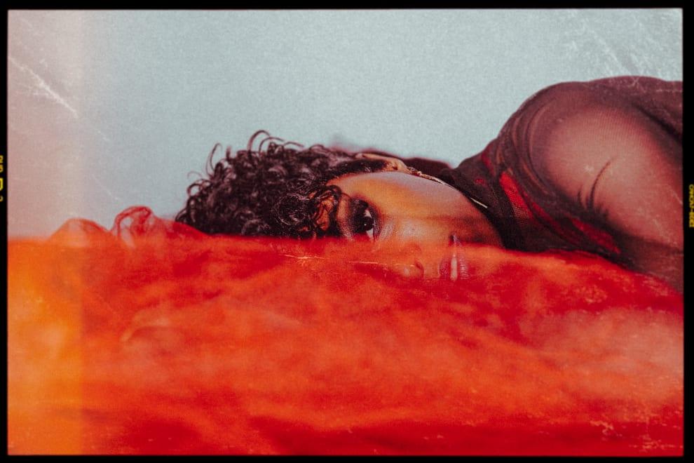 A colunista Stella Yeshua deitada em um tecido vermelho