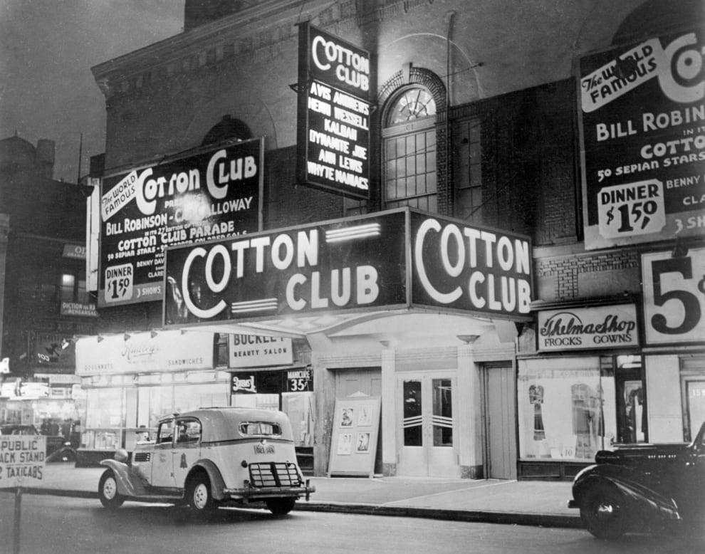 Foto em preto e branco. Na foto, está a fachada do Cotton Club. Há um carro antigo passando em frente ao local.