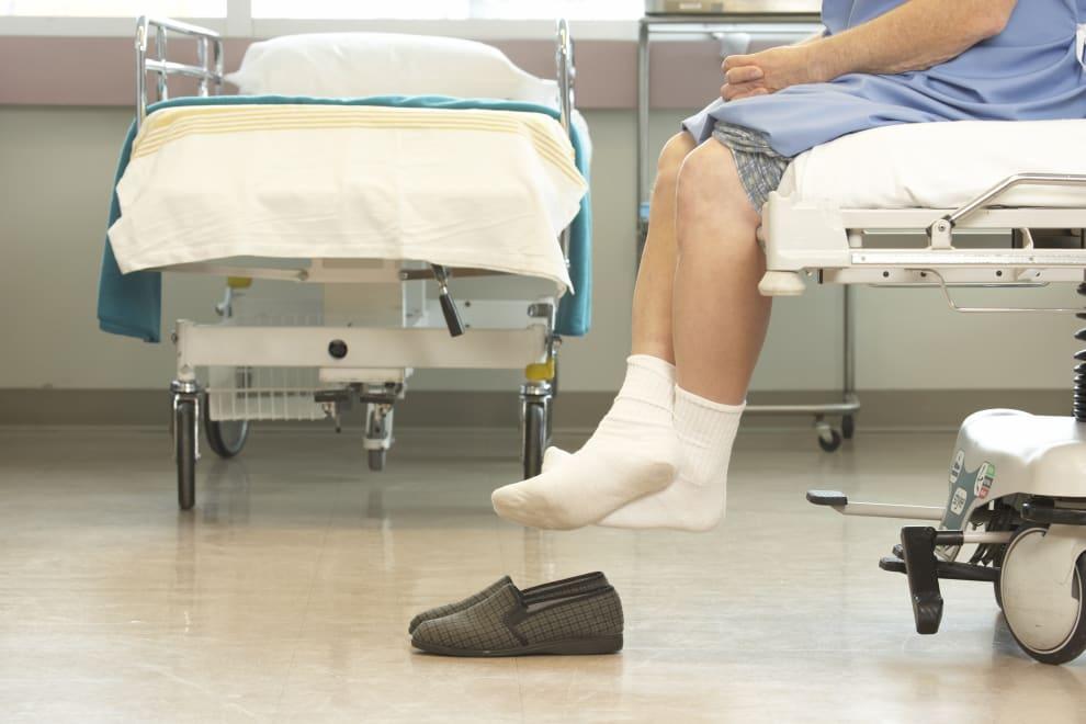 Penas de um paciente sentado em uma cama de hospital.