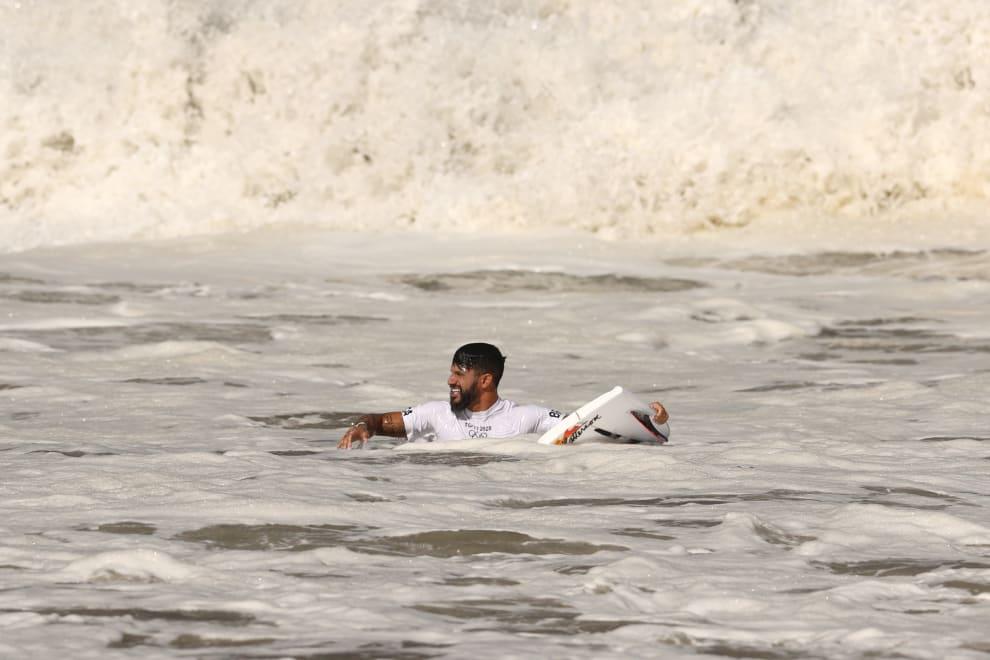 Ítalo Ferreira nadando no mar com uma prancha quebrada.