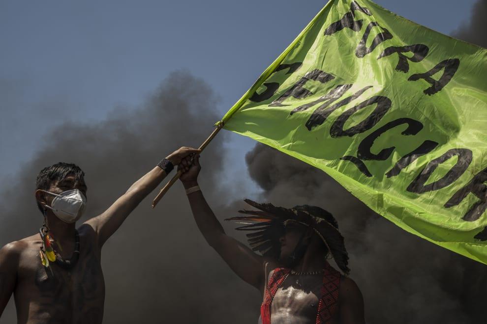 """Indígenas segurando uma bandeira com o escrito """"Fora Genocída""""."""
