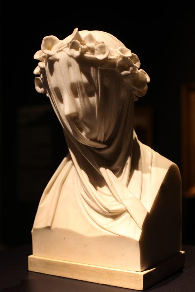 Busto de rosto feminino coberto com véu