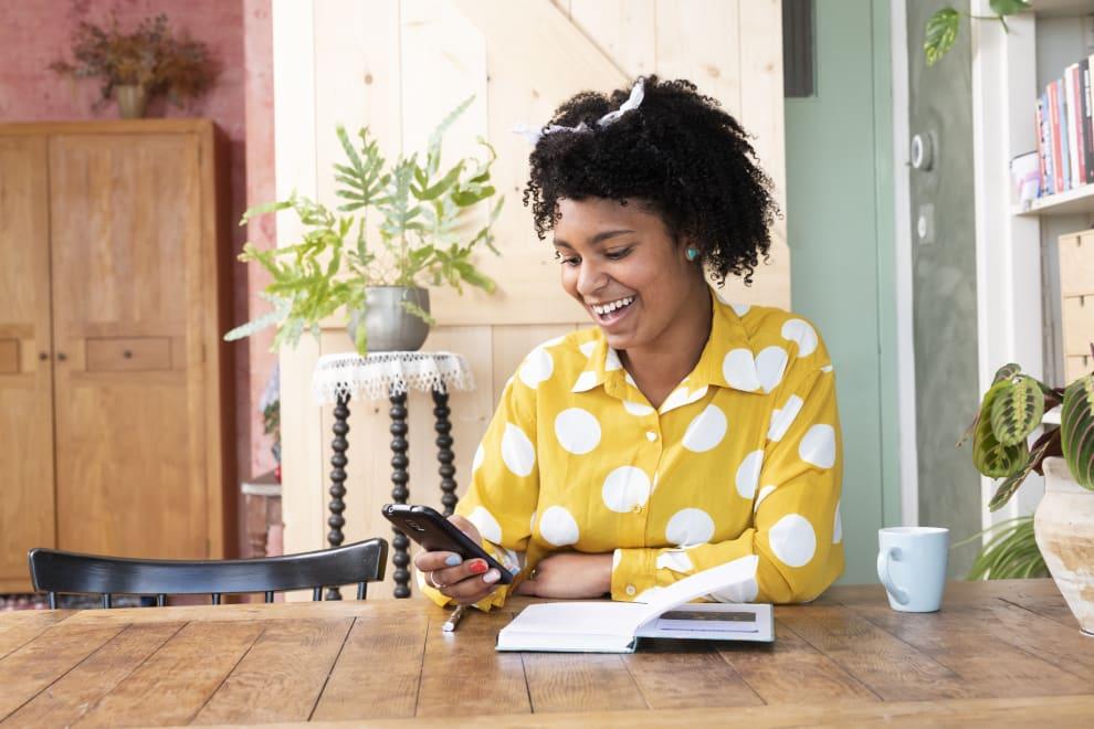 Na foo, uma mulher sentada olha para o seu celular enquanto sorri. Em sua frente, vê-se uma mesa onde há um caderno aberto.