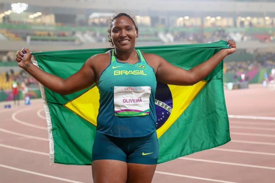 A atleta Andressa de Morais posa com a bandeira do Brasil.