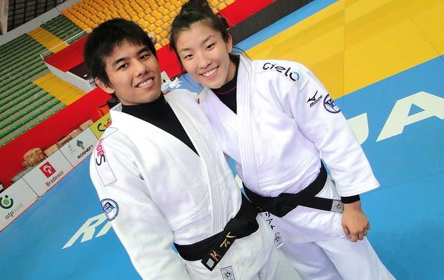 Os primos Charles e Gabriela Chibana estão posando para a foto. Ambos estão sorrindo e vestindo kimonos brancos, com faixas pretas. No fundo, aparecem os tatames e um pedaço da arquibancada.