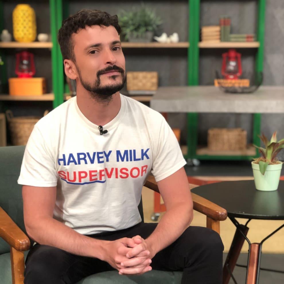 Fernando Oliveira está sentado e olhando para a câmera serenamente. Está vestindo uma camiseta branca e uma calça preta.