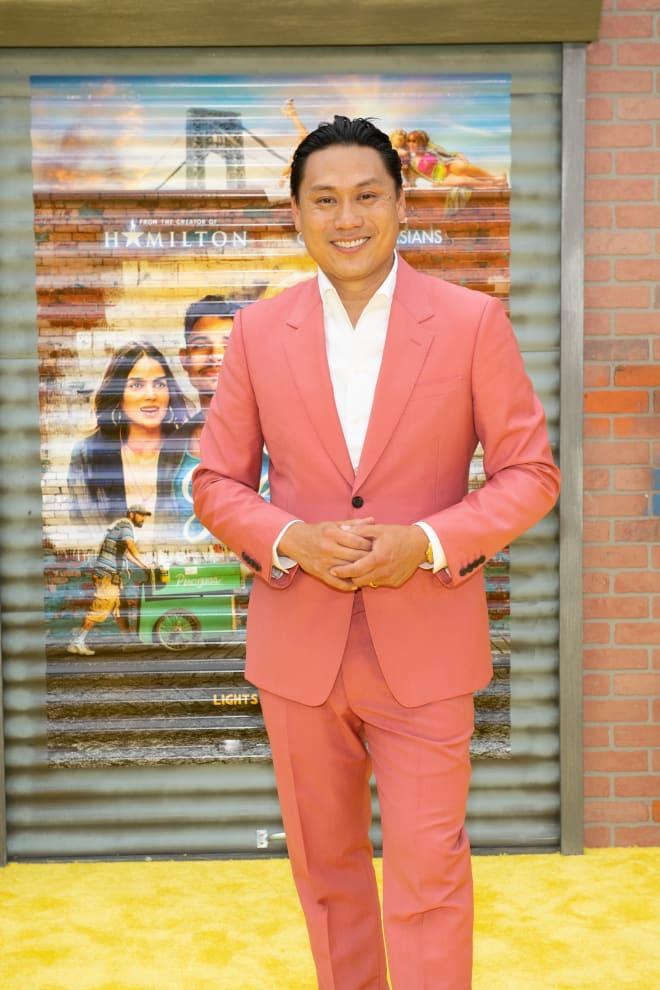 Jon na frente de um poster de In The Heights.