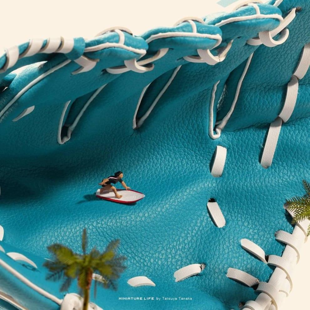 Uma luva de baseball azul simula uma onda para uma miniatura surfista.