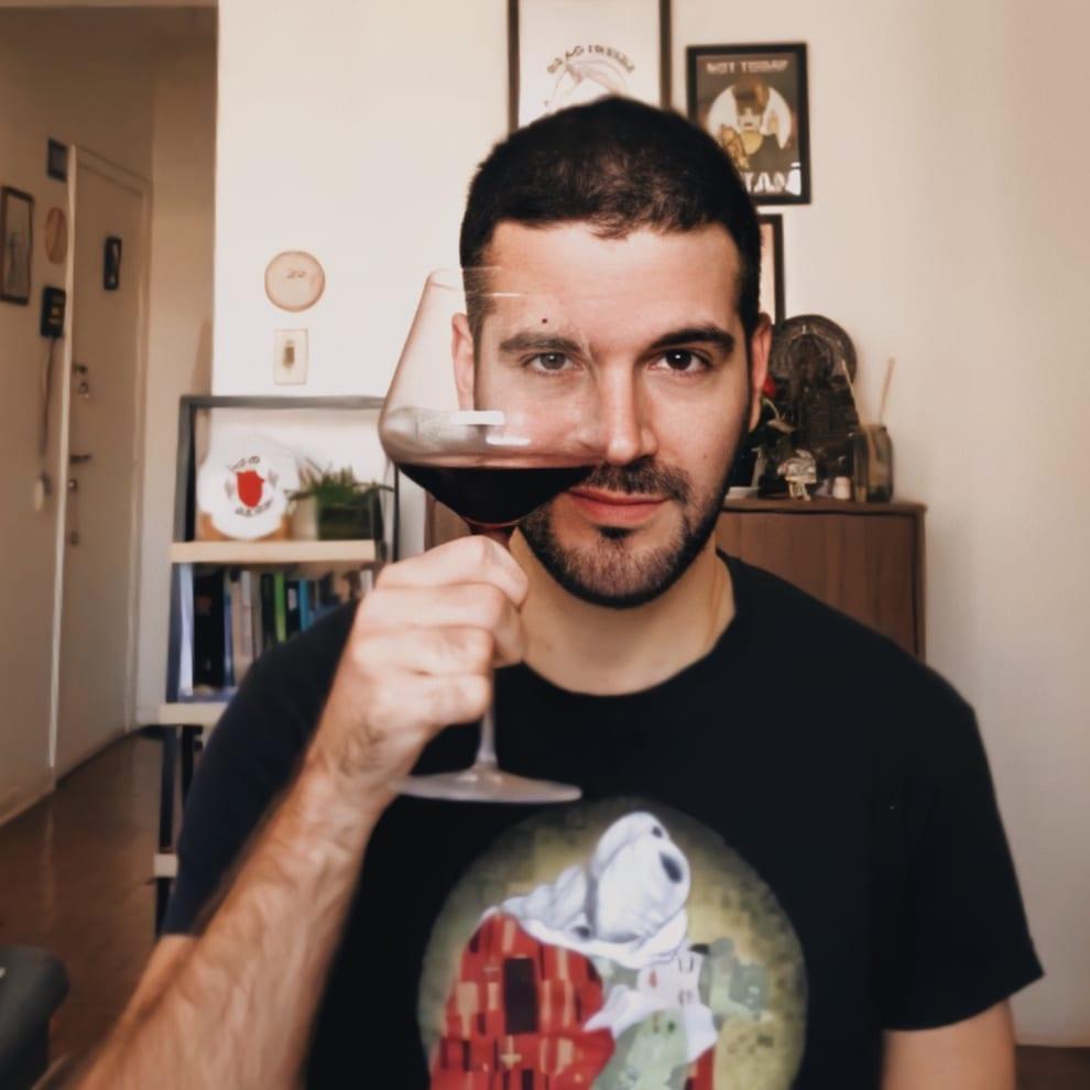 Bixa Bruxa está na sala de sua casa, olhando de frente pra câmera com uma taça de vinho à altura da cabeça, com um dos olhos atrás da taça