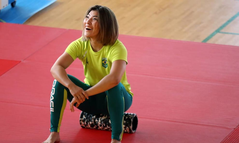 A atleta está sorrindo, sentada em um tatame vermelho. Aparentemente, descansando após um treino.