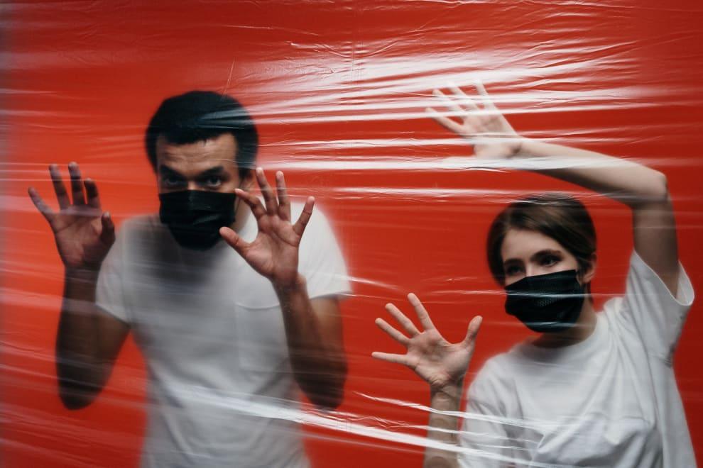 Homem e mulher, ambos de máscara, encostando em uma barreira de plástico filme.