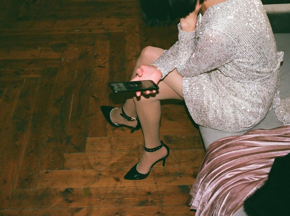 Mulher olhando para o celular, enquanto está de roupa de festa.