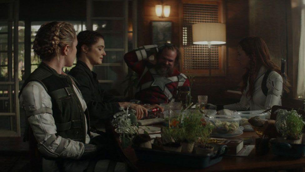 Viuva e diversos personagens novos sentados em uma mesa conversando