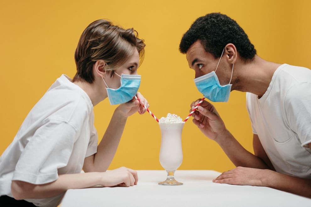 Homem e mulher de máscara, mas tomando um milkshake - casa um com seu canudo