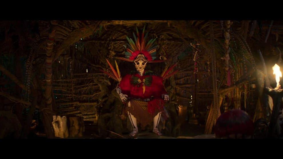 Cena do filme que mostra Sam, uma indígena, com vestes vermelhas e um crânio de animal cobrindo o rosto.