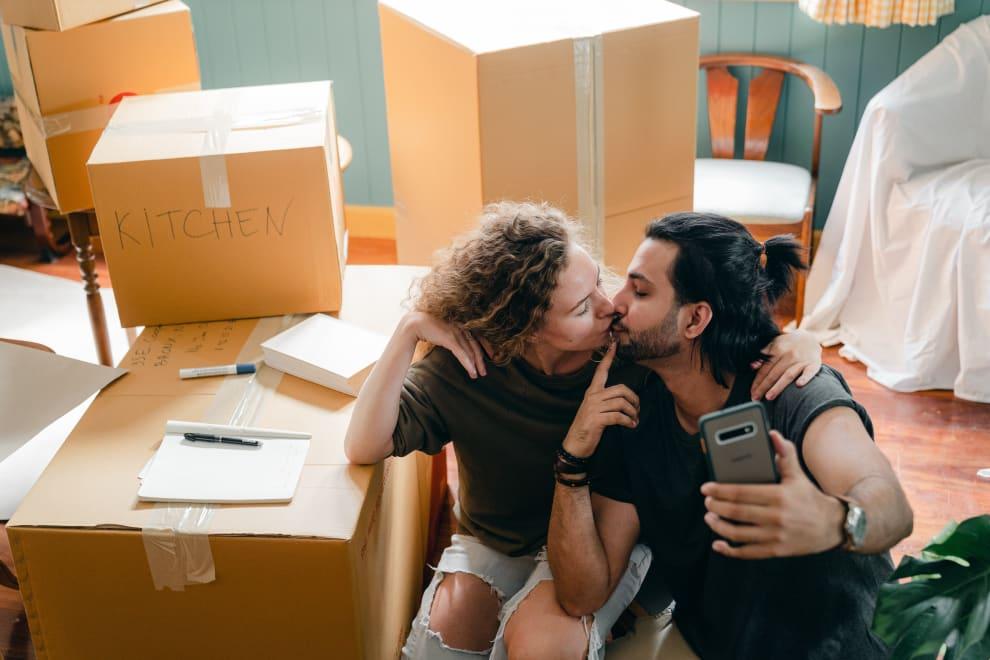 Casal se beijando enquanto tira uma selfie