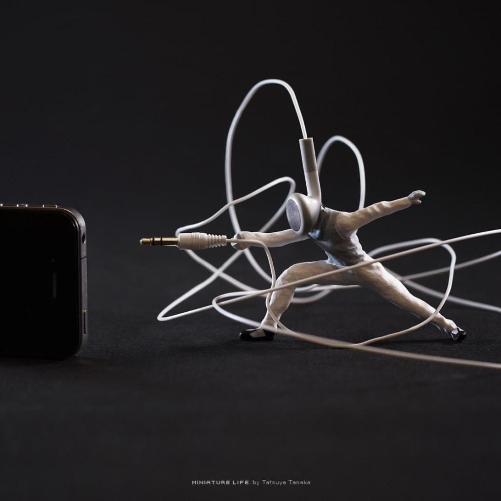 Uma miniatura segura um fone de ouvido, simulando uma luta de esgrima.