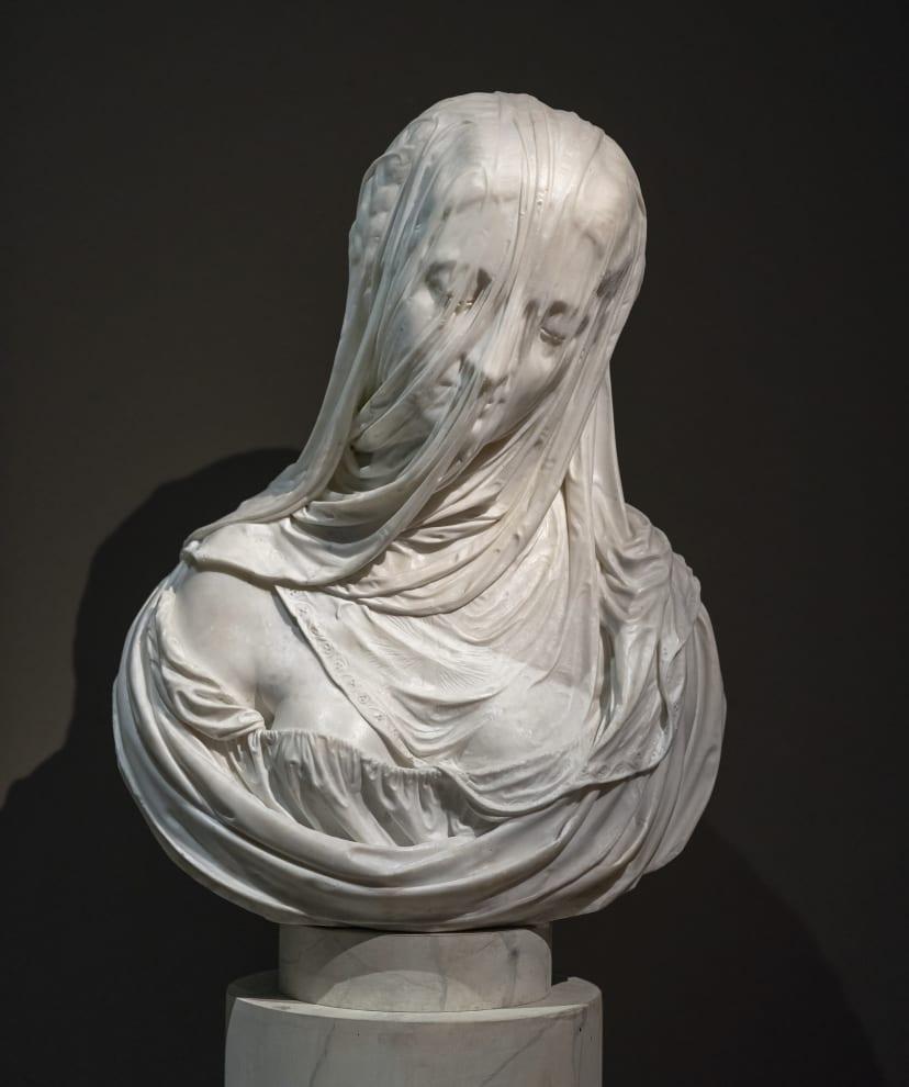 Um busto de mármore que parece estar coberto com um pano de seda, mas faz parte da escultura.