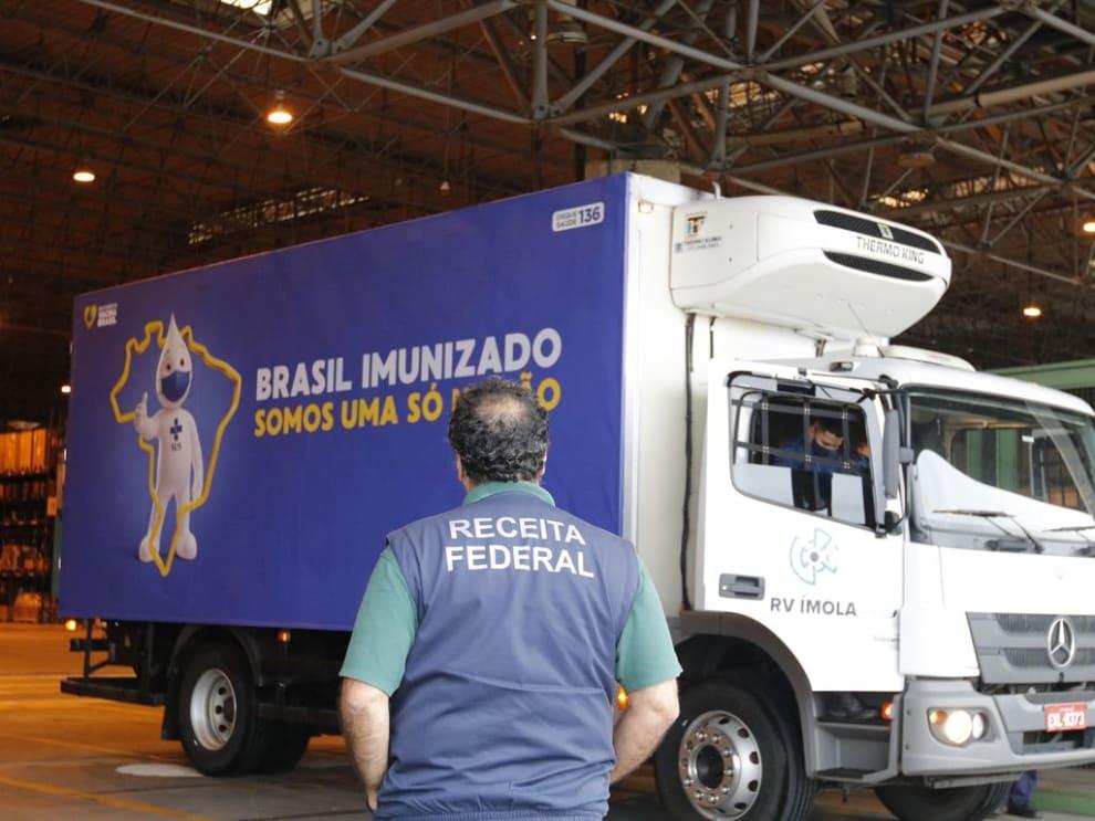 """Um caminhão com o Zé Gotinha e os dizeres """"Brasil iminizado, somos uma só nação˜. E um agente da receita federal em frente."""