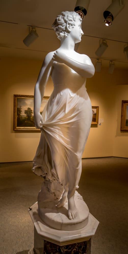 Escultura de Mulher puxando um vestido que flutua
