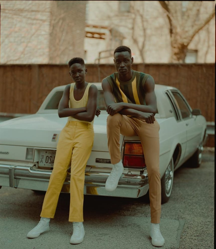 Um garoto e um homem, ambos negros, encostados em um carro antigo