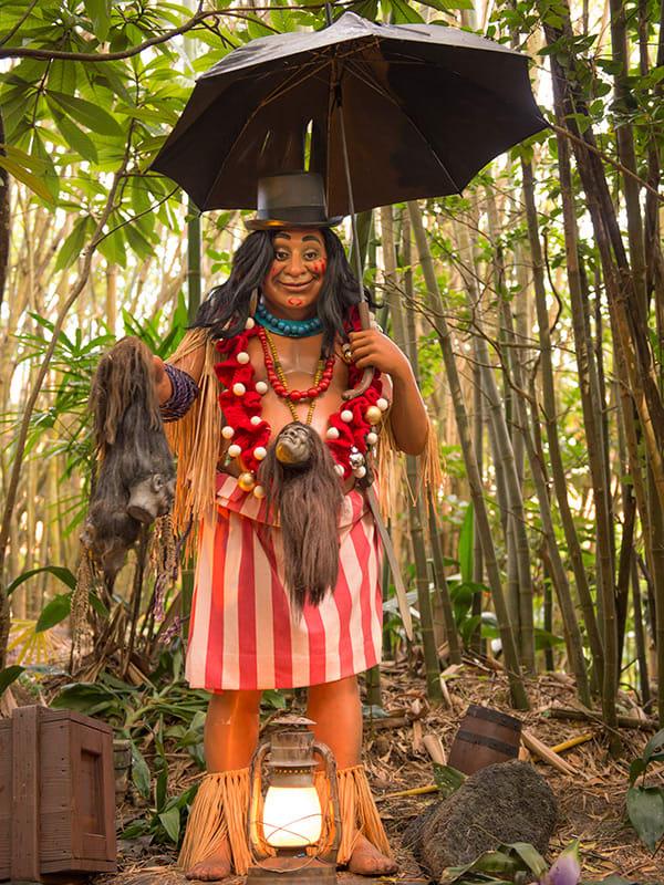 Estátua de Sam, uma mulher segurando cabeças encolhidas, usando um chapéu e um guarda-chuva.