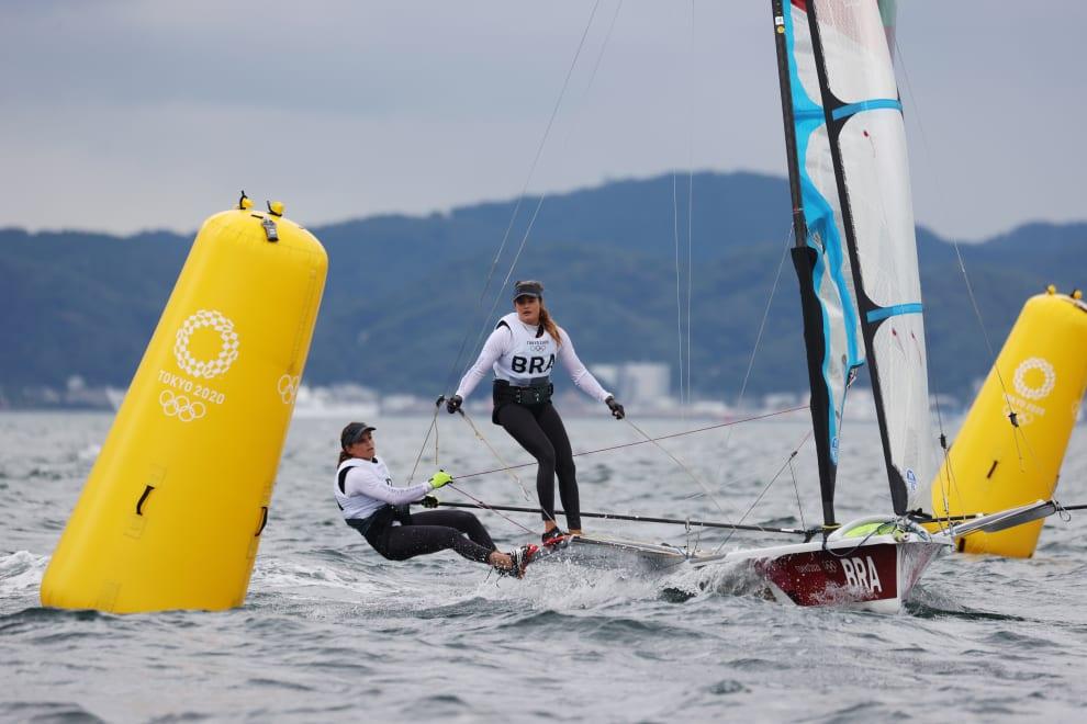 As duas atletas na vela, entre duas bóias gigantes.