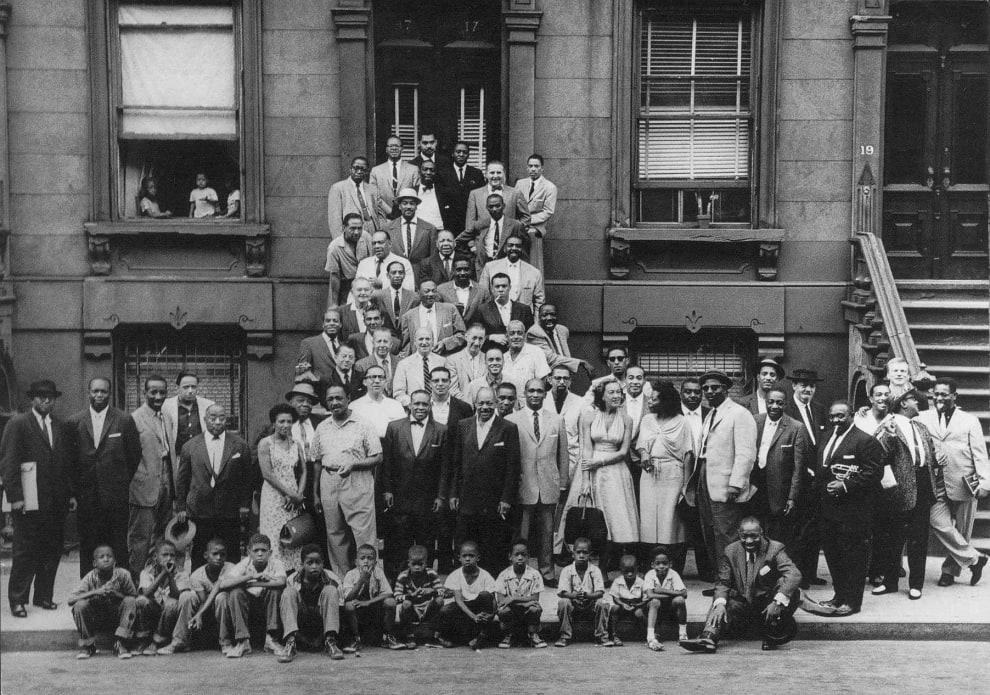 Foto antiga em preto e branco. Há diversas pessoas negras reunidas em frente a fachada de uma construção. Dentre elas, homens, mulheres e crianças.