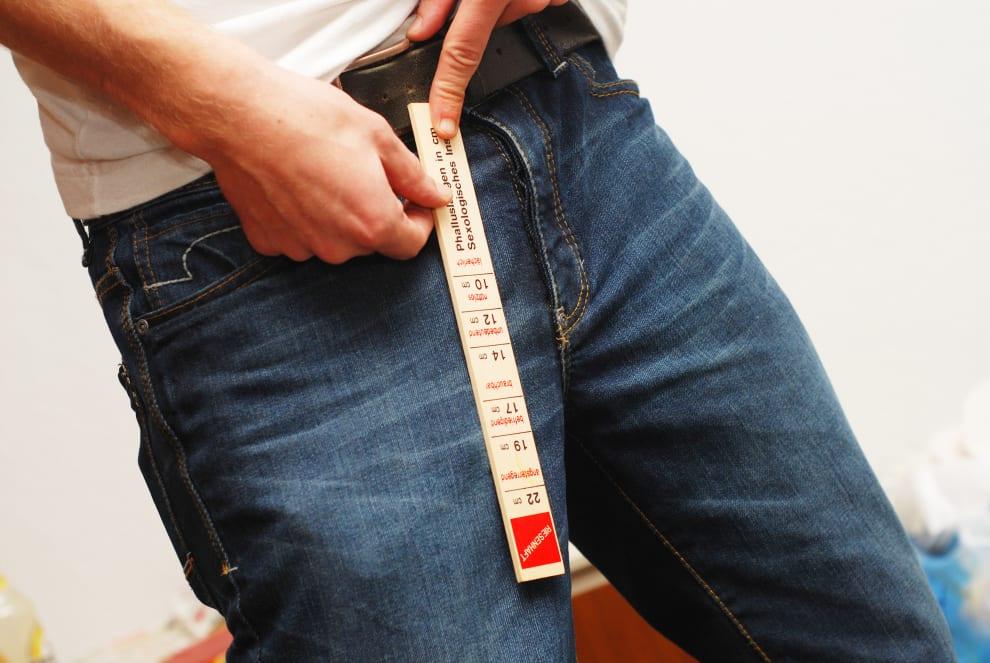 Homem com uma régua na frente da calça.