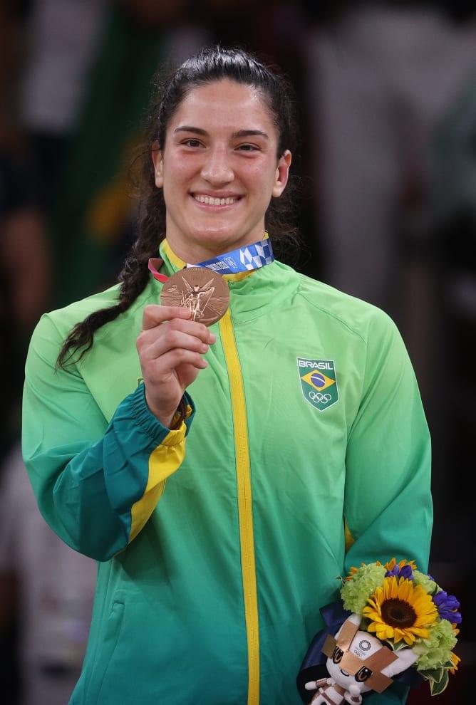 Mayra mostrando a medalha de bronze para as câmeras.