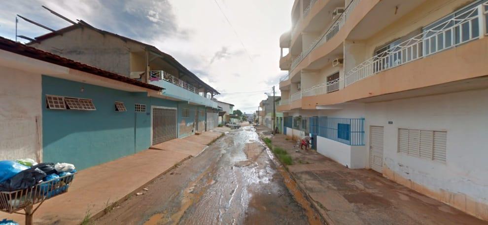Foto de rua asfaltada, mas cheia de barro e com sacos de lixo.