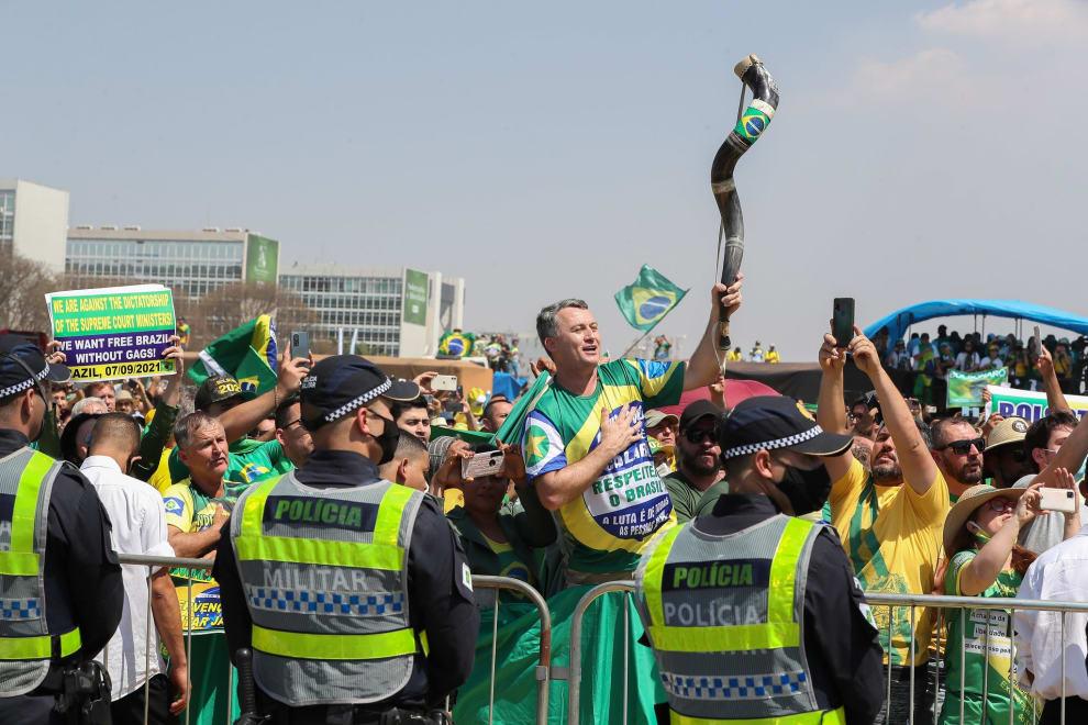Policiais em frente a uma multidão bolsonarista. Em destaque, um homem branco de meia idade coloca a mão no coração e segura um berrante.
