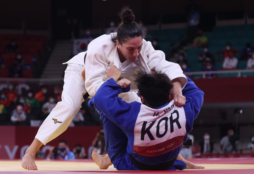 Mayra empurrando adversária sul coreana contra o tatame.