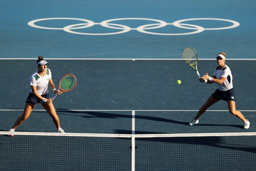 Luisa e Laura rebatendo uma bola.