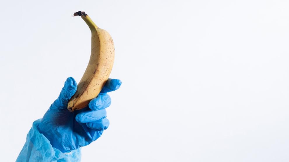 Luva médica segurando uma banana